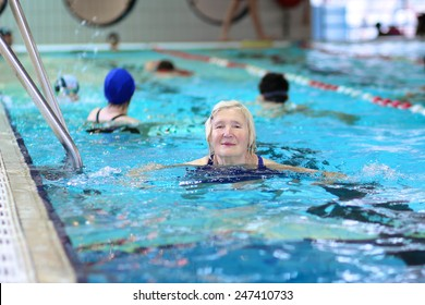 Group of happy healthy senior women enjoying sportive lifestyle swimming in the pool - active retirement concept