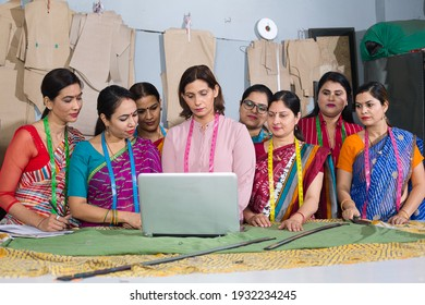 Group of happy Indian woman using laptop by sewing machine at textile factory