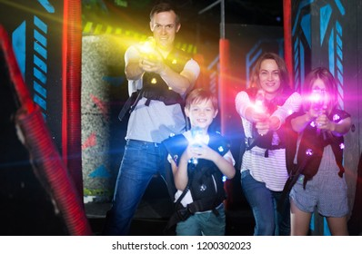 Group of happy kids and adults having fun on dark lasertag arena in colorful beams of laser guns