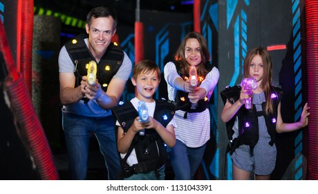 Group of happy kids and adults with laser guns having fun on dark lasertag arena