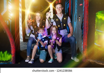 Group of happy kids and adults posing together in colorful beams of laser guns while having fun on dark lasertag arena