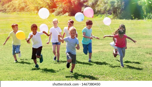 Group of happy kids with balloons running in race and laughing in park