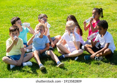 Group of happy kids drinking water and sitting on grass in park outdoors