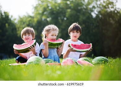 Group of happy kids eating watermelons outdoor. Summer healthy food.