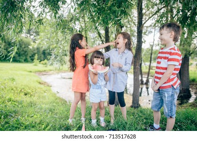 group of happy kids eating watermelons in park