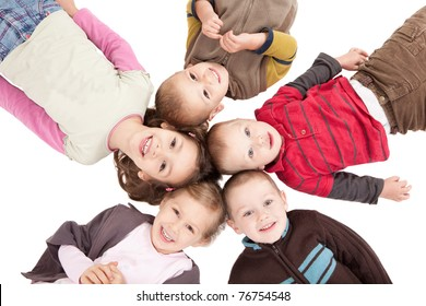 Group of happy kids lying on backs on isolated white floor.