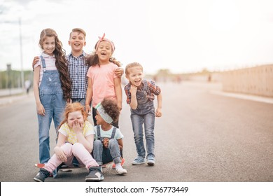 group of happy kids outdoors. redhead girl and african girlsitting on skateboard. the concept of friendship and intercultural communication