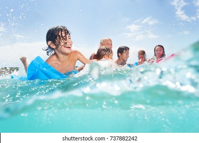 Group of happy kids play in the sea on matrass