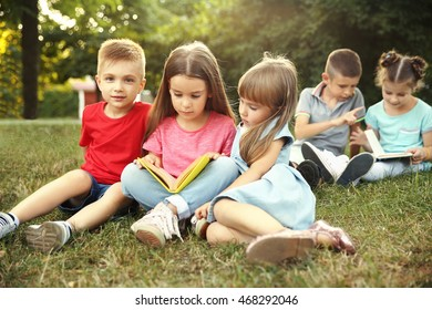 Group of happy kids reading books in park