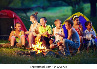 group of happy kids roasting marshmallows on campfire