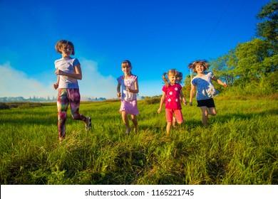 Group of happy kids running in green summer field