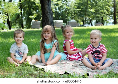 group of happy kids sitting on the green grass and having fun in the park, best friends playing outside in summer, happy family concept
