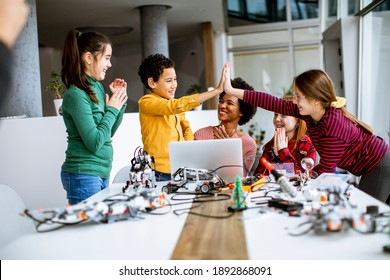 Group of happy kids with their African American female science teacher with laptop programming electric toys and robots at robotics classroom