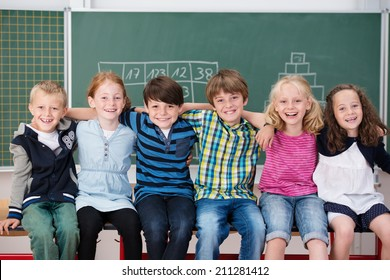 Group of happy laughing children in school sitting in a long row in front of the blackboard with their arms around each others shoulders