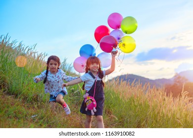 group of Happy little girls holding colorful balloons. Child playing on a green meadow. Smiling kid, beautibull sky sunset in backbround