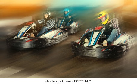 Group of happy male and females in helmets driving racing cars at kart track