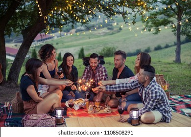 Group of happy millennials have fun with fire sparkles at picnic in spring at sunset on a camping holiday. They drinking wine and eating meat prepared at the barbecue