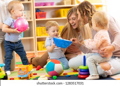 Group of happy moms with their babies in nursery