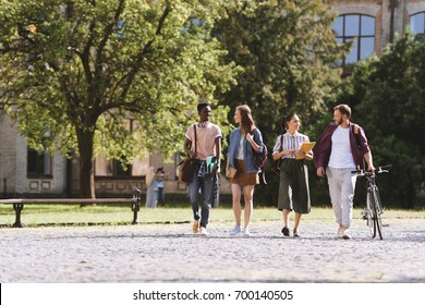 group of happy multicultural students walking together in park