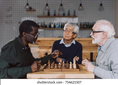 group of happy multiethnic senior friends playing chess at cafe