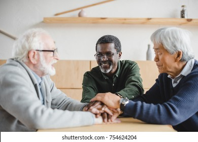 group of happy multiethnic senior friends making team gesture and looking at each other
