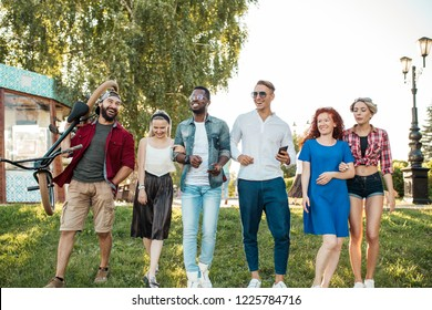 Group of happy multiracial co-workers wearing stylish clothing going to the outdoor corporative party in park on summer sunny day. Leisure, holidays, people, fun and happiness concept.