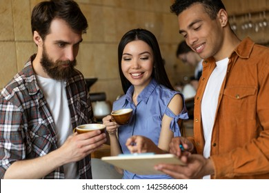 Group of happy multiracial friends drinking coffee together in cafe, communication, talking, discussing creative ideas. Coffee break concept. Smiling hipsters working project, cooperation, teamwork