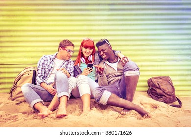 Group of happy multiracial friends having fun together using mobile smart phone - Young hipster people addicted by smartphone on social network community - Multicolored halos on vintage filtered look