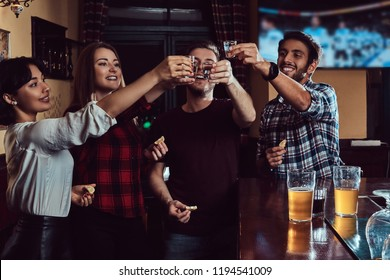 Group of happy multiracial friends making a toast with vodka while standing at bar or pub.