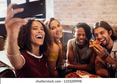 Group of happy multiracial friends taking selfie on a smart phone while having party at pizza restaurant. Excited friends taking selfie with phone while hanging out at restaurant.