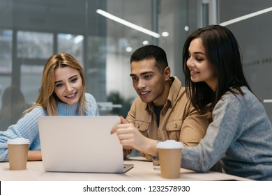 Group of happy multiracial university students studying together, working project, using laptop computer for learning language online. Online education concept. Hipsters friends searching information.