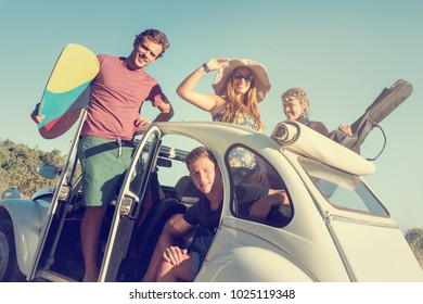 Group of happy people in a car in summertime ready for a roadtrip.