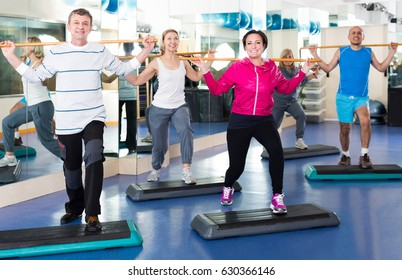 Group of happy people exercising in a fitness club