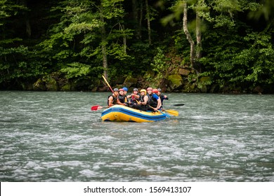 Group of happy people with guide whitewater rafting and rowing on river. Russia, Guziripl, September 2019.