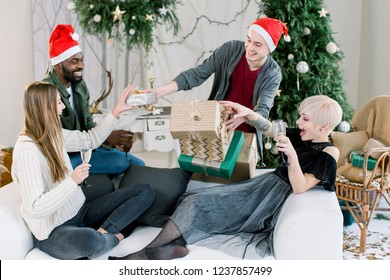 Group of happy people having a great time, celebrating New Year. Two girls and african boy sitting on white sofa and drinking champagne, and white boy behind is giving Christmas presents for them