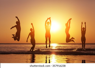 Group of happy people jumping in the sea at sunset, concept about having fun on the beach, silhouette