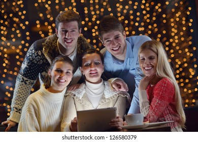 Group of happy people looking at a tablet computer