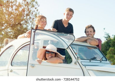 Group of happy people near a car in summertime, retro style.
