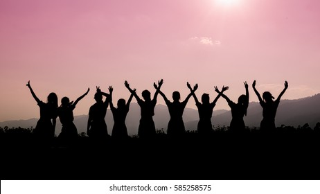 Group of happy people playing at summer sunset in nature