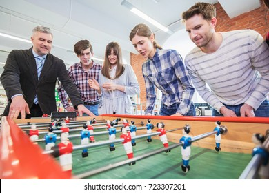 Group of happy people playing table soccer together