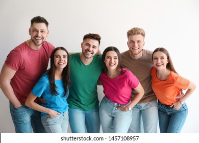 Group of happy people posing near light wall