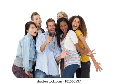 Group of happy people singing into microphone over white background