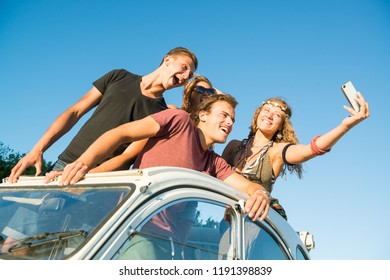 Group of happy people taking a selfie in a car at sunset in summer.