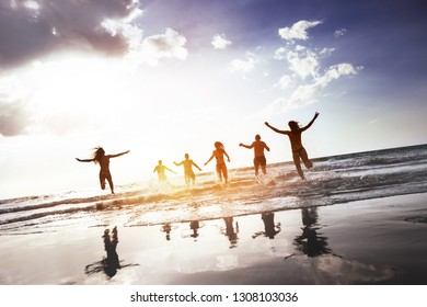 Group of happy peoples runs and jumps at sunset sea beach. Tropical tourism concept