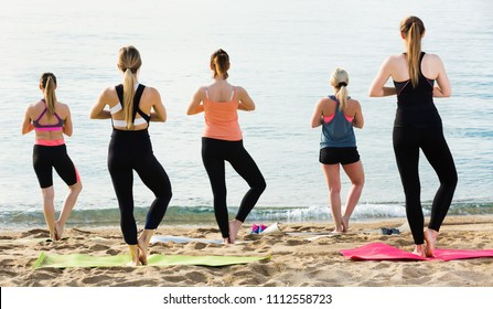 Group of happy  positive females performing yoga on beach and looking at smooth sea