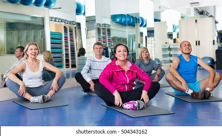 Group of happy positive smiling mature people exercising on sport mats in a fitness club