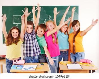 Group of happy school child  in classroom.