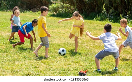 Group of happy schoolchildren playing football together in park