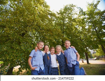 Group of happy schoolkids looking at camera in park