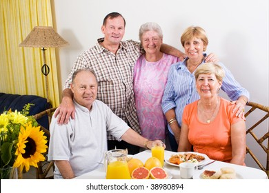 group of happy senior friends at breakfast table